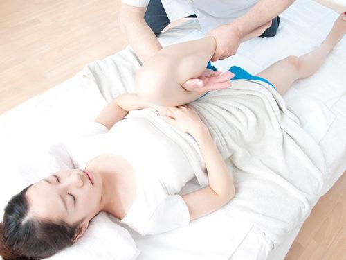 女性の膝を曲げる施術者