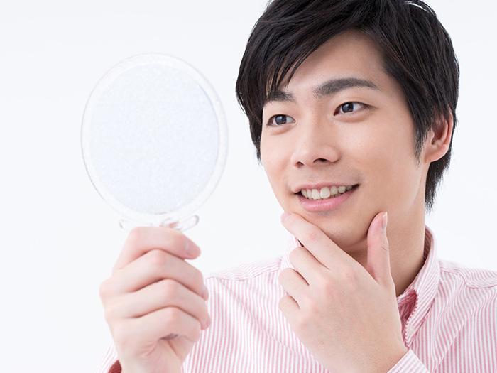 顎を触りながら鏡を見る男性